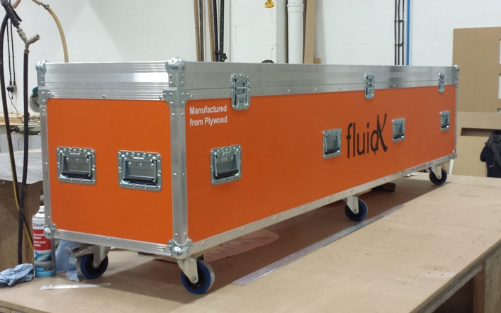 An orange laminated, custom built, flight case with six castors sitting on a workbench
