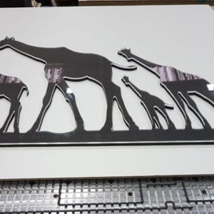 A 2D CNC cut clear acrylic over black MDF piece of wall art showing four Giraffes