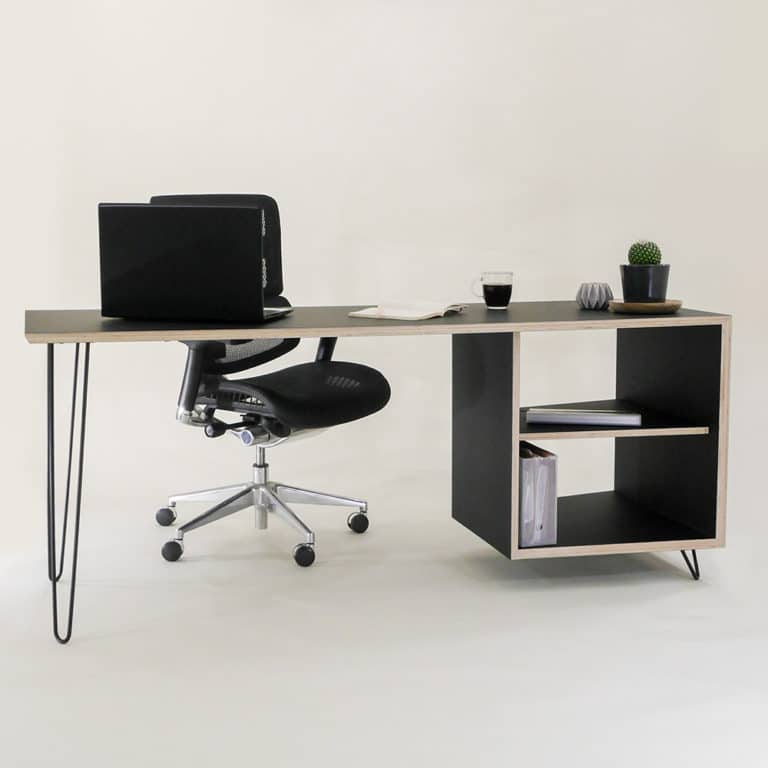 A custom built bespoke black laminated plywood desk on hairpin legs with an office chair and dressed with props for photo graphic purposes