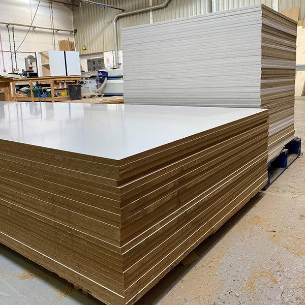 Two stacks of White Melamine Faced board the one in the foreground are uncut MF MDF the one behind is Melamine Faced Chipboard which has been cut to size and edged with ABS Edging