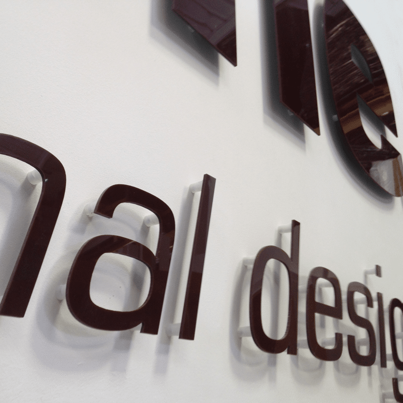 Brown cnc acrylic letters cut to shape and fitted to a wall with standoffs