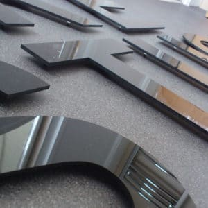 A close up photo of CNC cut black acrylic letters mounted on standoffs