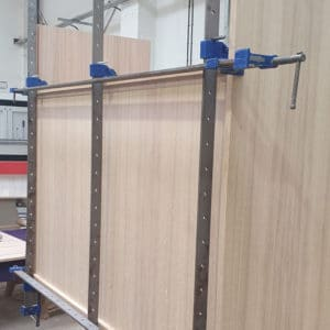 A partially built Oak veneer faced MDF display cabinet in production with long sash clamps holding it together whilst being glued