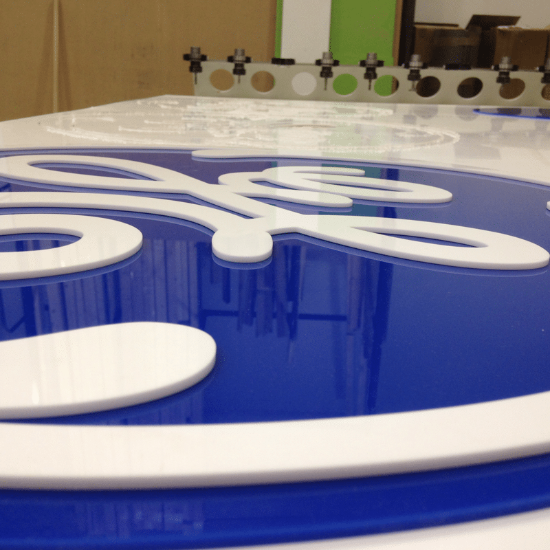 A GE logo cut from white and blue perspex and laying on top of a CNC machine