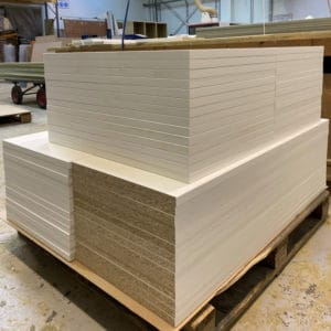 A stack of white Melamine faced chipboard panels cut to size and edged sat in a workshop environment
