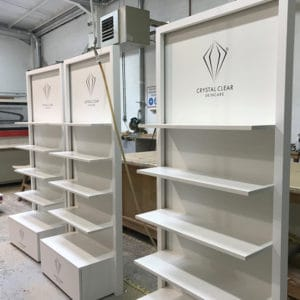 Three white laminated bespoke FSDU's sitting in a workshop awaiting deliver to the customer