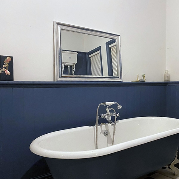 Painted blue bead and butt panels in a bathroom with a freestanding roll-top bath