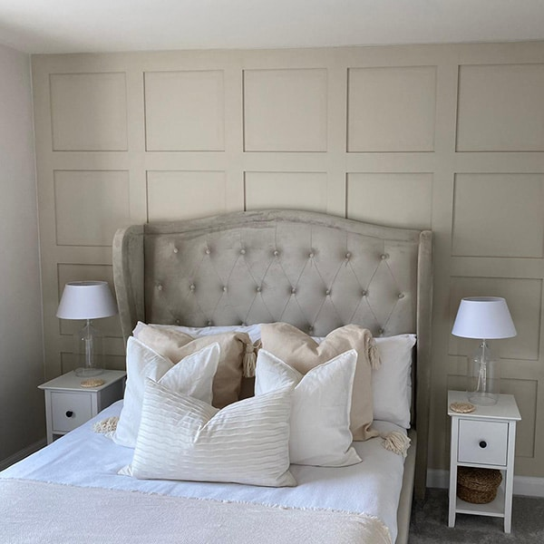 a photo of a taupe coloured bedroom with shaker style wall panelling