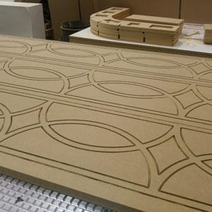 CNC fret cut MDF screen panels sitting on a CNC router bed