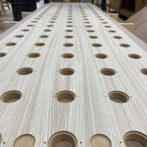 A CNC perforated Oak Veneer faced MDF panel on a workbench