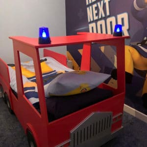 A child's Fire engine shaped bed made from MDF featuring blue flashing lights on the roof